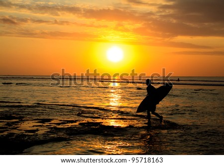 A surfer walking on the beach at sunset - stock photo