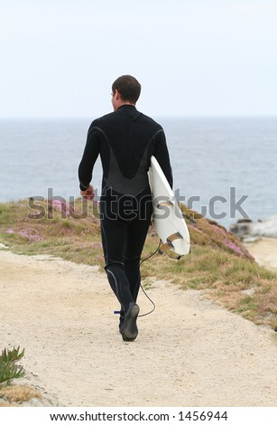 A surfer walking out to the waves to surf - stock photo