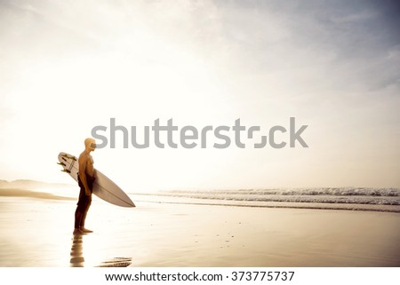 A surfer with his surfboard at the beach - stock photo
