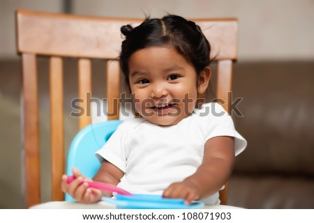 A surprised little girl holding a spoon and sitting in a high chair - stock photo