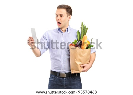 A surprised man looking at store receipt and holding a paper bag isolated on white background - stock photo