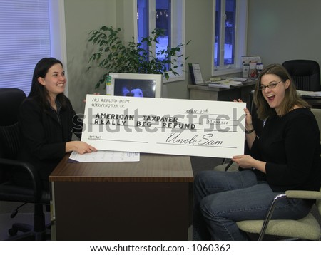 A surprised woman receives an oversized tax refund check. - stock photo