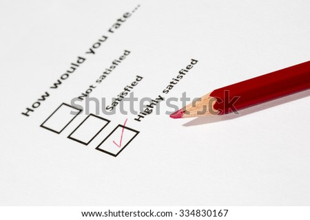 A survey form filled with a red pencil. The form is asking for opinion whether the person would rating something. The answer is highly satisfied. The focus point is on the red pen tip. - stock photo