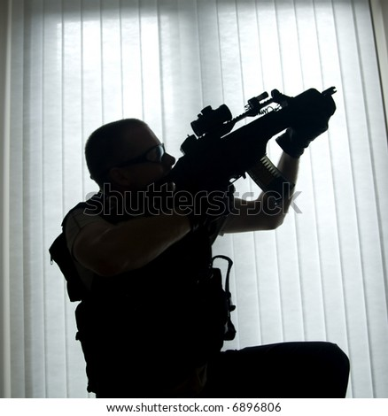 a swat police officer with a mp5 machine gun - stock photo