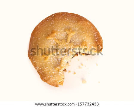 A sweet Christmas mince pie with a bite out of it on a white background. - stock photo