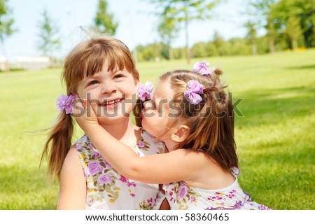 A sweet girl kissing her elder sister - stock photo