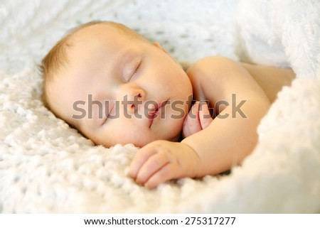 A sweet newborn infant girl is sleeping peacefully while snuggled in warm white blankets - stock photo