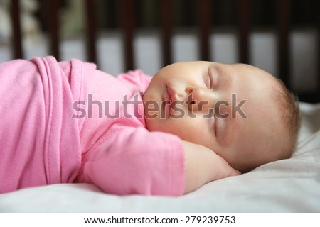 A sweet one month old newborn baby girl is sleeping on her back in her crib, swaddled in a pink blanket. - stock photo