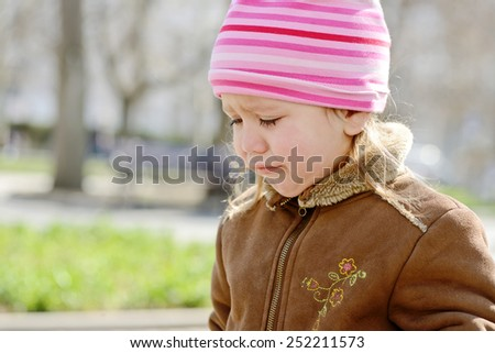 a sweet toddler girl is crying outdoors - stock photo