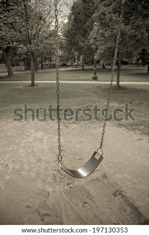 A swing with dirt under it, and trees and light poles in the background. - stock photo