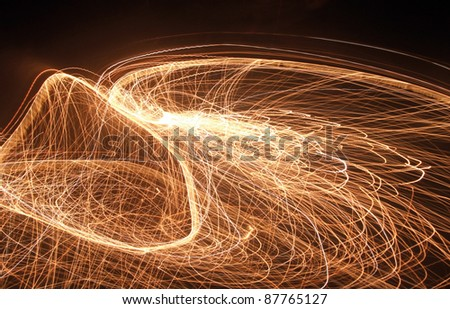 a swinging colorful pyrotechnic effect in dark back - stock photo