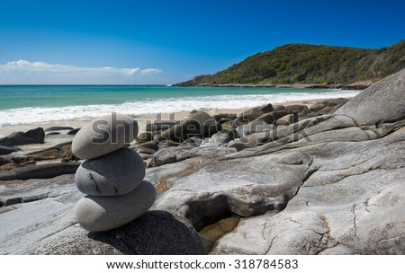 A Symbolic Man Made Stone Pile Also Known As Cairn, Placed On The Beach And Overlooking The Noosa National Park During Summer At Granite Bay, Noosa Heads, Queensland, Australia - stock photo