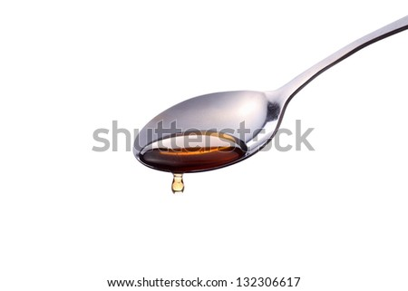 a syrup liquid pours off of a metal spoon - stock photo