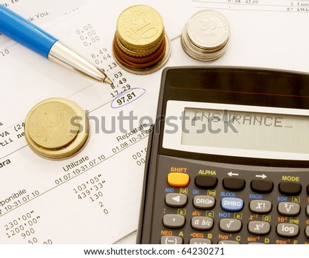 A table full of bills with a pen, some coins and a calculator that displays the word insurance - stock photo