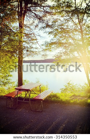 A table set by the beach in Finland. People can enjoy their snacks by the lake while traveling with their cars on holiday. Image has a vintage effect applied. - stock photo