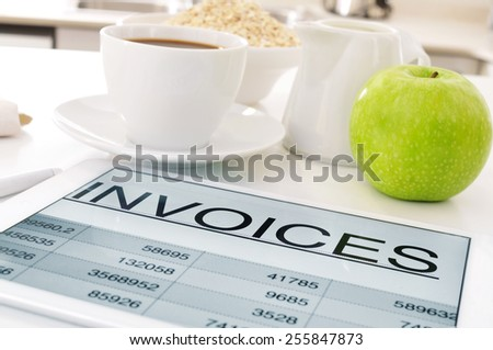 a tablet computer with a spreadsheet of invoices and a cup of coffee, a bowl with cereals and an apple on the kitchen table - stock photo