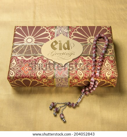 A tag with 'Eid Mubarak' message in english on a golden gift box along with islamic prayer beads - stock photo