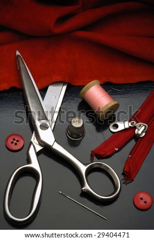 a tailors tools - scissors, needle, thimble, spool of thread, etc. - on black table - stock photo