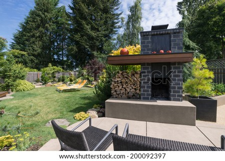 A tall, custom-designed fireplace with grey bricks and plenty of firewood sits on an inviting patio with a beautifully landscaped yard in the background. - stock photo