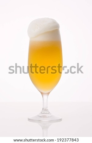 A tall glass of beer with a frosty head. - stock photo