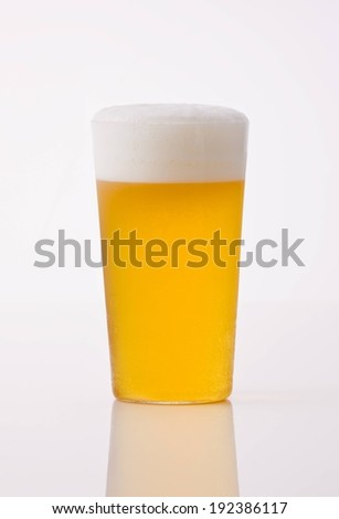 A tall glass of beer with a one inch foamy head on it. - stock photo