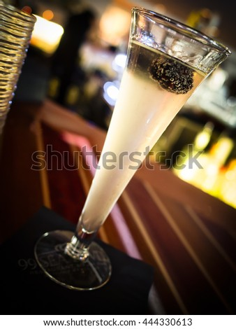 A tall summer cocktail glows on a polished bar. - stock photo