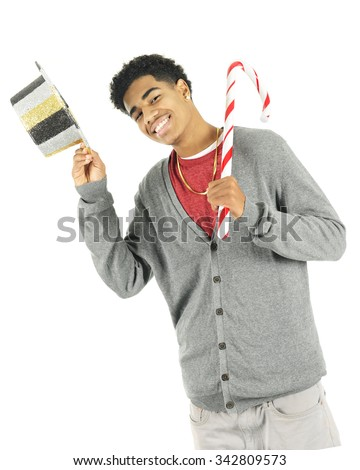 A tall teen boy holding a giant candy cane while tipping a New Year's Eve hat.  On a white background. - stock photo