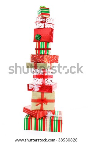 A tall tower of Christmas gifts wrapped in colorful paper and ribbons. - stock photo