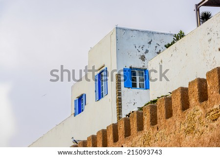 A tall white building surrounded by battlement style brick gate - stock photo