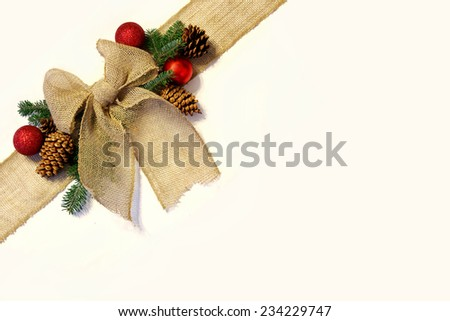 A tan colored burlap holiday ribbon is tied into a bow in the corner, wrapped around a Christmas present, surrounded by pine cones, tree branches and holiday ornaments, isolated on white background. - stock photo