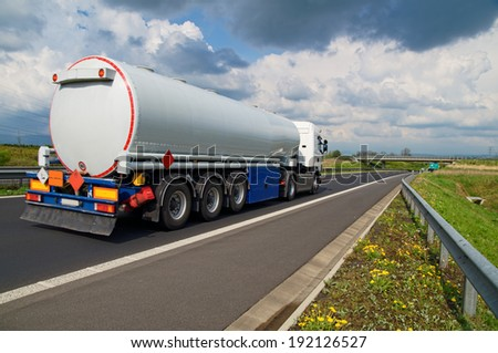 A tanker truck on the highway leading through the countryside, in the background the bridge over the highway, on the hard shoulder of blossoming flowers, dramatic clouds - stock photo