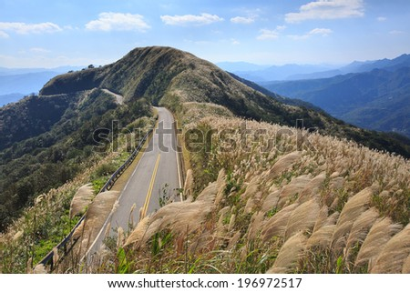A tarmac road stretching out over the tops of the mountains. - stock photo