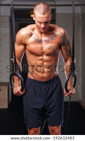 A tatooed muscled man doing pullups on rings - stock photo