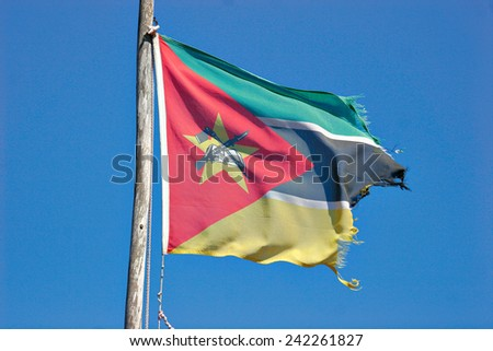 A tattered Mozambique flagger flutters on a flagpole. - stock photo