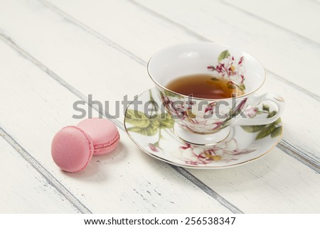 A tea cup with two macarons (macaroon) on a white wooden table. Vintage Style. - stock photo