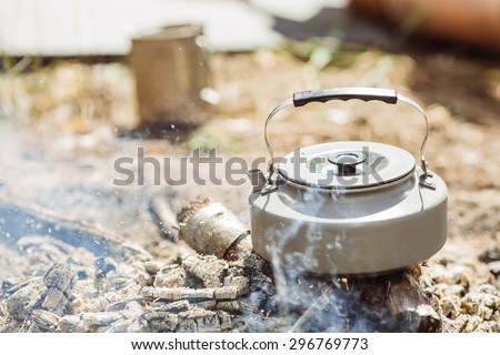 A tea kettle boiling over hot coals - stock photo
