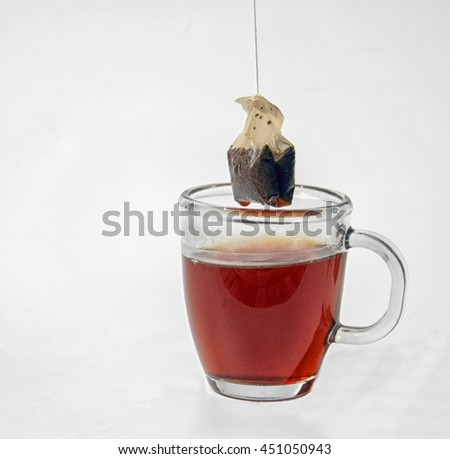a teabag is taken out of a cup of tea - stock photo