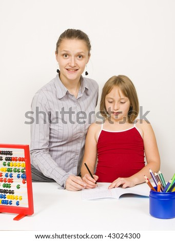 A teacher and a student learning together in the school, colored pencils on a blue recipient against white wall. The  teacher smiling to the camera, the student paying attention on what she writes. - stock photo
