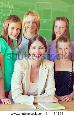 A teacher posing with her students in the classroom. - stock photo