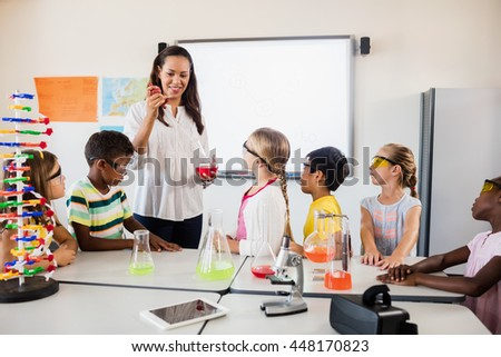A teacher teaching a science lesson in classroom - stock photo
