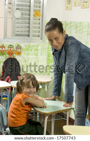 A teacher with a student in a classroom.  They are facing the camera and are smiling. Vertically framed shot. - stock photo