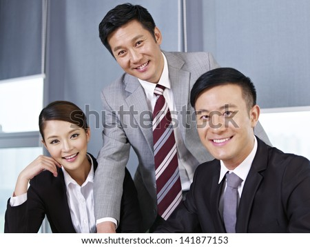 a team of asian business people looking at camera and smiling. - stock photo