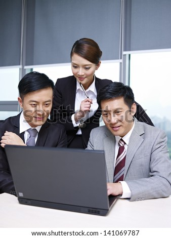 a team of asian business people working together in office. - stock photo