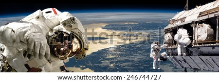 A team of astronauts performing work on a space station while orbiting over Earth. The sun reflects off the surrounding waters.  Elements of this Image Furnished by NASA. - stock photo