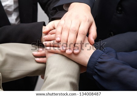 A team of business people hold their hands make union - stock photo