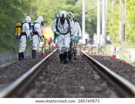 A team working with toxic acids and chemicals is approaching a chemical cargo train crash near Sofia, Bulgaria. Teams from Fire department are participating in a training with spilled toxic materials. - stock photo