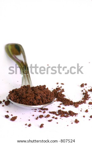 A teaspoon of instant coffee, with alot of white background to add additional own writing/pics - stock photo