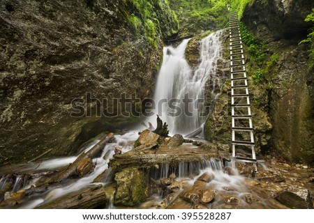 A technically aided trail along a waterfall in a lush gorge in Slovensky Raj in Slovakia. - stock photo
