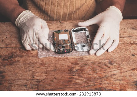 A technician is fixing and replacing the broken screen on a smart phone - stock photo