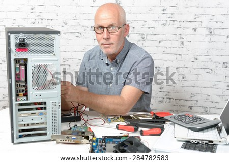a technician repairing a computer with different tools - stock photo